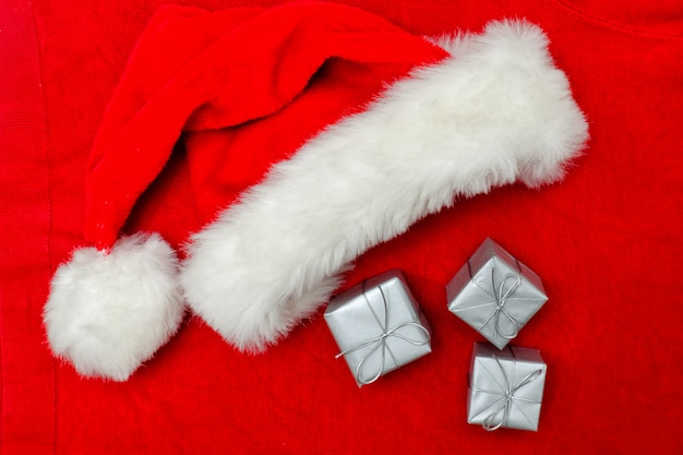 Santa hat and silver boxes on a red background