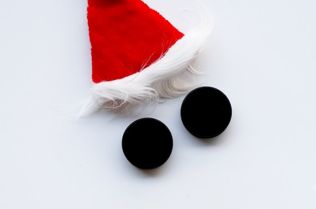 Santa hat and two hockey puck like eyes on white background hockey santa top view flatlay