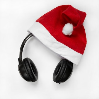 Santa hat with headphones, xmas concerts, events isolated flat lay top view