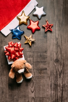 Santa hat with metallic stars, present and teddy bear on wooden background.