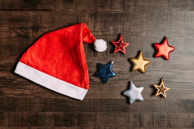 Santa hat with metallic stars on wooden background.