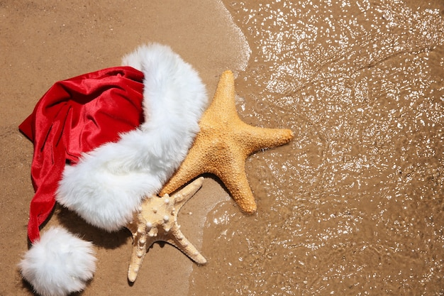 해변에서 바다 별과 산타 모자입니다. 크리스마스 휴가 개념