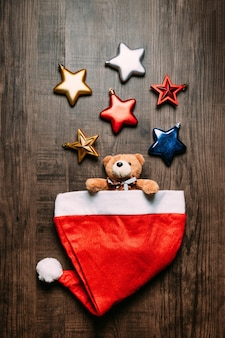 Santa hat with teddy bear inside and metallic stars on wooden background.