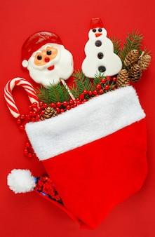 Шляпа санта-клауса с традиционными рождественскими конфетами на красном фоне