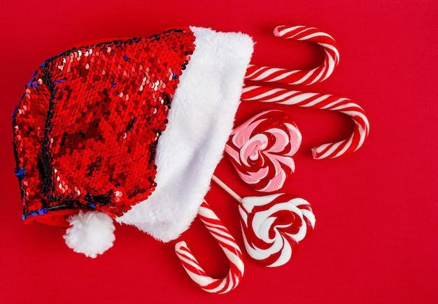 赤い背景に伝統的なクリスマスキャンディーとサンタの帽子