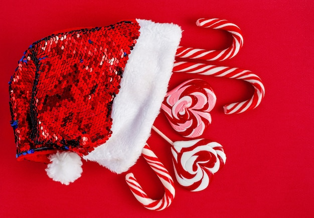 Santa hat with traditional christmas candies on red background