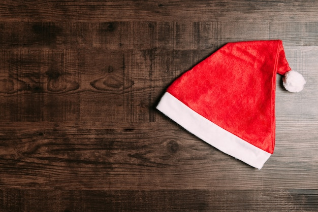 Santa hat on wooden background. flat lay for christmas and happy new year banner.