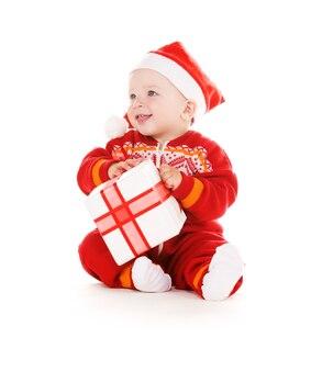白い壁の上のクリスマスプレゼントとサンタヘルパーの赤ちゃん