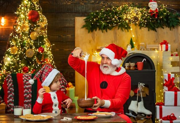 サンタヘルパーかわいい小さな子供の男の子とパパは、クリスマスツリーのメリクリの近くでジンジャーブレッドクッキーを作ります...