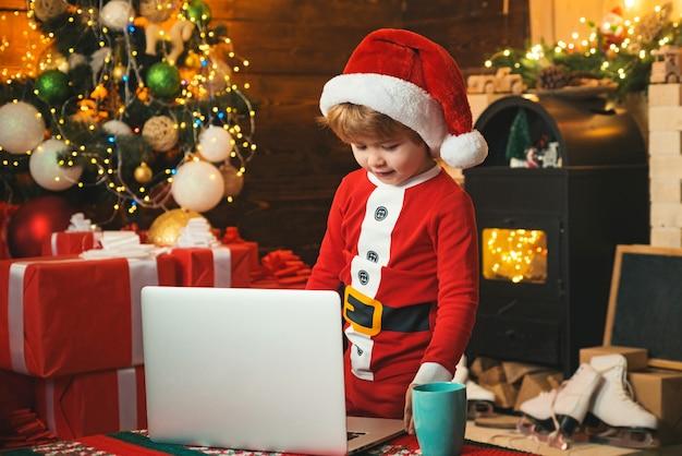 ノートブックを使用してサンタヘルパー。サンタさんへの子供タイプの手紙。かわいい夢のようなサンタヘルパーの肖像画