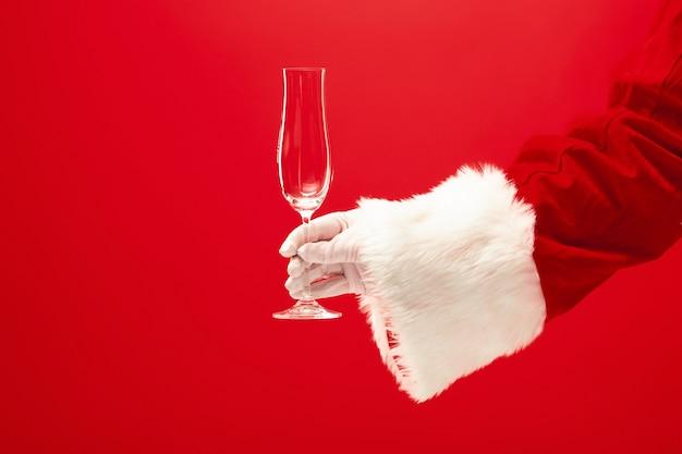 赤い背景の上にシャンパンワイングラスを保持しているサンタ。季節、冬、休日、お祝い、ギフトのコンセプト