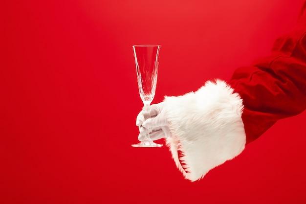 赤い背景の上のサンタ持株シャンパンワイングラス。季節、冬、休日、お祝い、ギフトのコンセプト