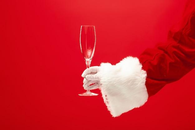 Bicchiere da vino santa holding champagne su sfondo rosso. stagione, inverno, vacanza, celebrazione, concetto di regalo
