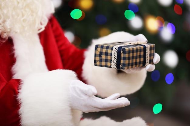 Санта держит подарок на фоне елки