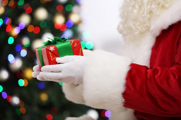 クリスマスツリーの背景にギフトを保持しているサンタ