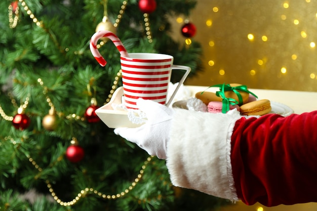 Santa holding mug and plate with cookies in his hand, on bright background