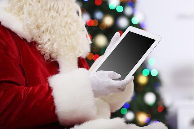 クリスマスツリーにタブレットを保持しているサンタ