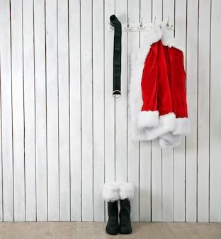 木製の白い壁にサンタのジャケット、ブーツ、ベルト