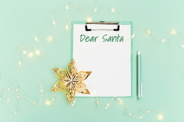 Santa letter with text dear santa on white sheet of paper, new year garland