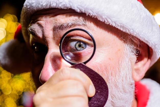Santa looks through lens santa claus looking through magnifying glass at christmas bearded santa