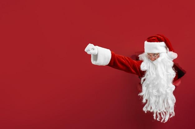 Санта-мужчина пробивает дыру в бумаге, как супермен. место для текста. праздничный дизайн плаката, баннер.
