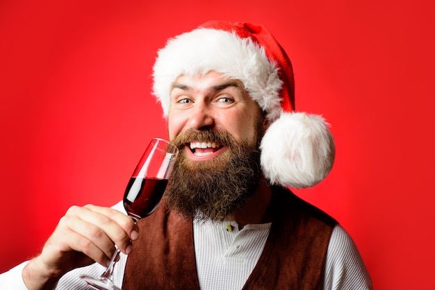 산타 모자에 레드 와인 사업가의 산타 남자 음료 유리 수염 난된 남자 시음 와인 잔을 잡아