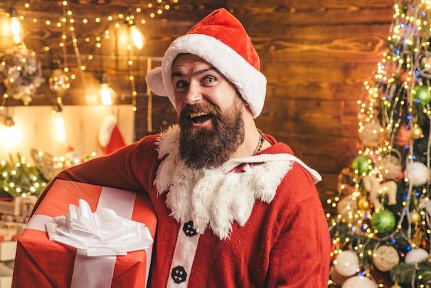 贈り物を持っているサンタの男。流行に敏感な男、ひげを生やしたサンタは感謝祭の日とクリスマスを祝います。ヒップスター