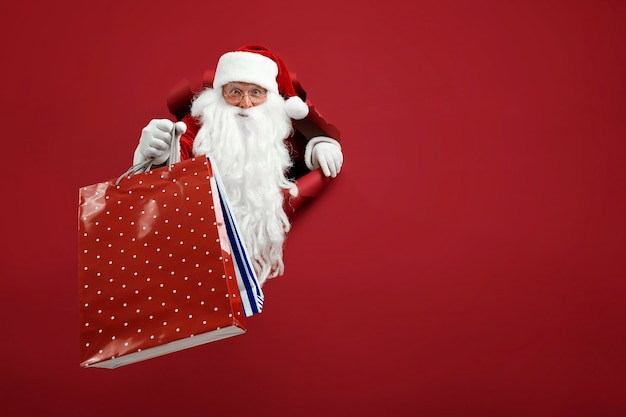 Santa man holds shops packet in hand through a paper hole. bearded man in santa hat looking through hole on red paper.