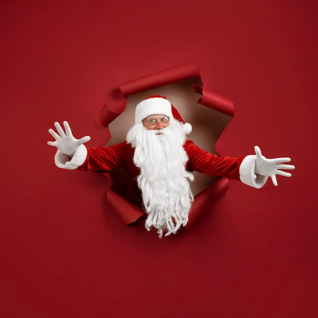 Santa man spread his arms in different directions and look emotionally through a paper hole. bearded man in santa hat looking through hole on red paper.