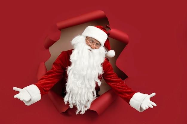 Санта-мужчина развел руки в разные стороны и эмоционально смотрел сквозь дырочку в бумаге. бородатый мужчина в новогодней шапке, глядя через отверстие на красной бумаге.