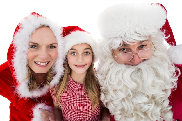 Santa and mrs claus smiling at camera with little girl