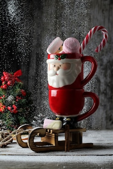 Santa mug full of marshmallow and candy caneover wooden sled