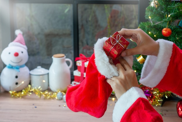 Santa put the gift box in santa's sock, against christmas decoration background