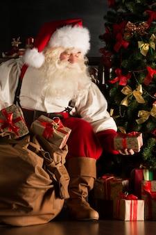 Санта кладет подарки под елку в темной комнате