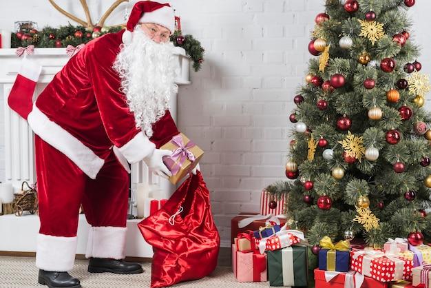 산타 크리스마스 트리 아래 선물을 퍼 팅