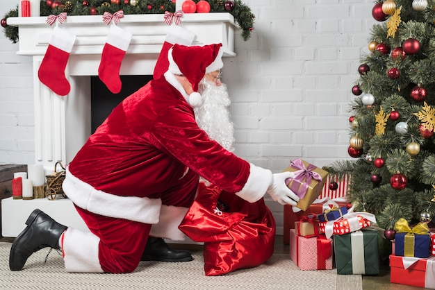 Santa putting presents under christmas tree