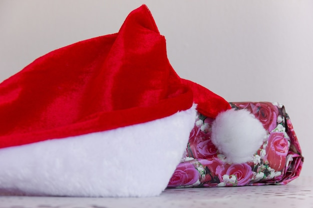 Santa red hat by gift with floral wrap christmas holiday season present invisible friend concepts