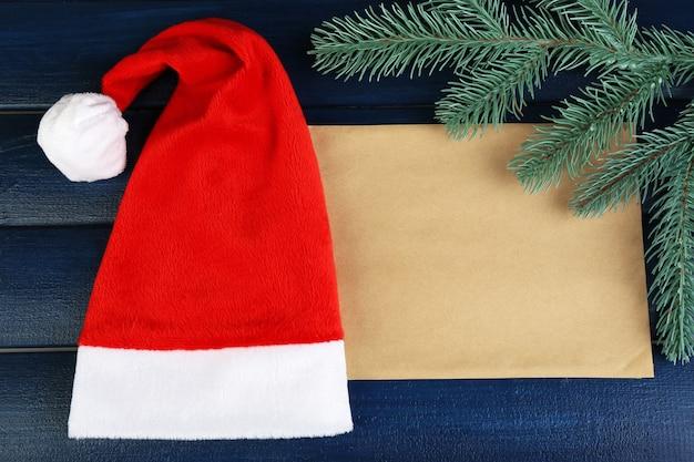 Красная шляпа санта-клауса с веткой елки и листом бумаги на цветном деревянном фоне