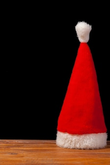 The santa red hat on wooden table on black background