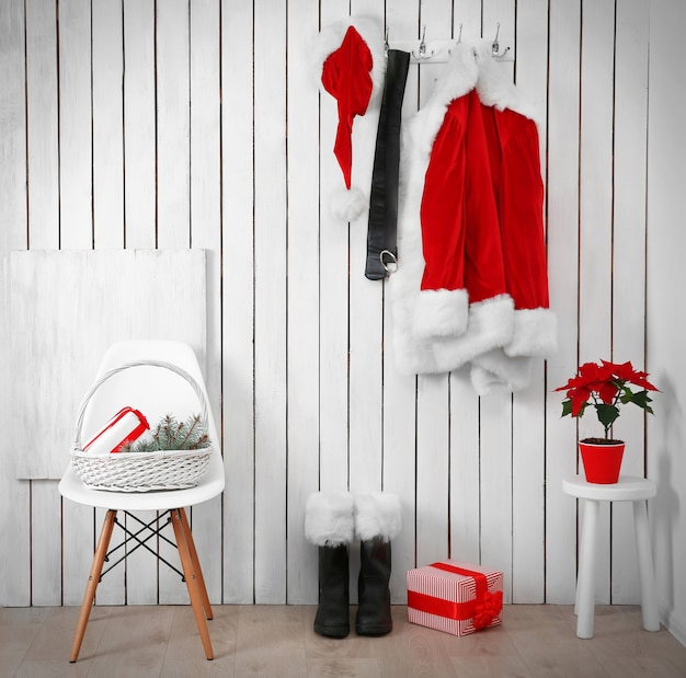 木製の白い壁にサンタの赤いスーツ
