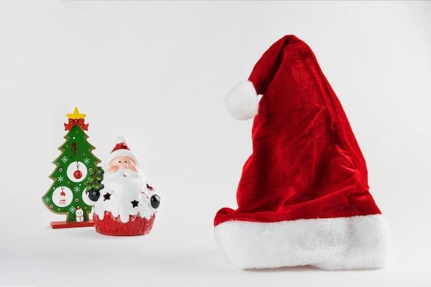 Шапка санты и дед мороз, изолированные на белом фоне. рождественский орнамент. выборочный фокус.