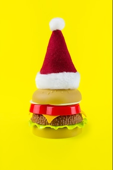 黄色の背景におもちゃのハンバーガーとサンタの帽子。 2021年の新年のサイン。ギフト包装ハンバーガー