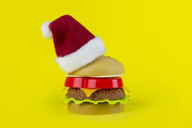 黄色の背景におもちゃのハンバーガーとサンタの帽子。クリスマスのファーストフード。ギフト包装ハンバーガー