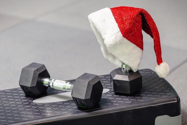 체육관에서 산타의 모자. 크리스마스와 새 해에 스포츠의 개념입니다. 피트니스, 건강하고 활동적인 라이프 스타일 개념.