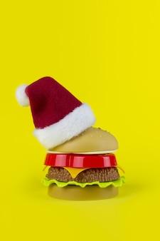 黄色の背景にクリスマスツリーの形でプラスチックハンバーガーにサンタの赤い帽子。サンタクロースが大好き