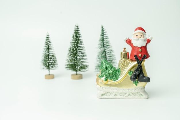 산타는 크리스마스 트리 앞에서 아이스 스케이트에 앉아 행복의 축제를 기다리고 있습니다.