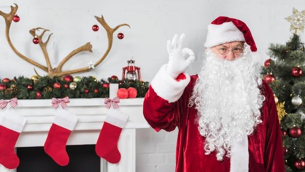 Santa showing okay gesture near fireplace