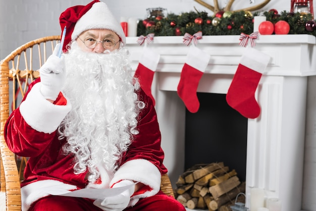 Santa sitting in chair with wishlist and pen