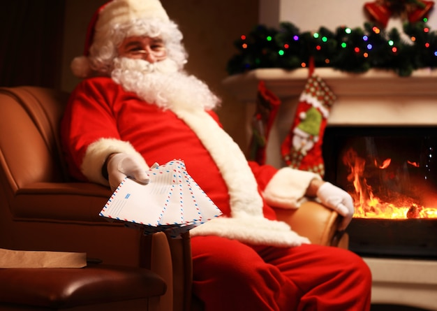 Santa sitting at the christmas tree, holding christmas letters and having a rest by the fireplace. home decoration