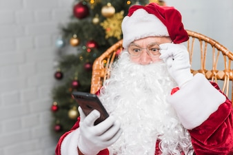 Santa sitting on rocking chair and looking at phone